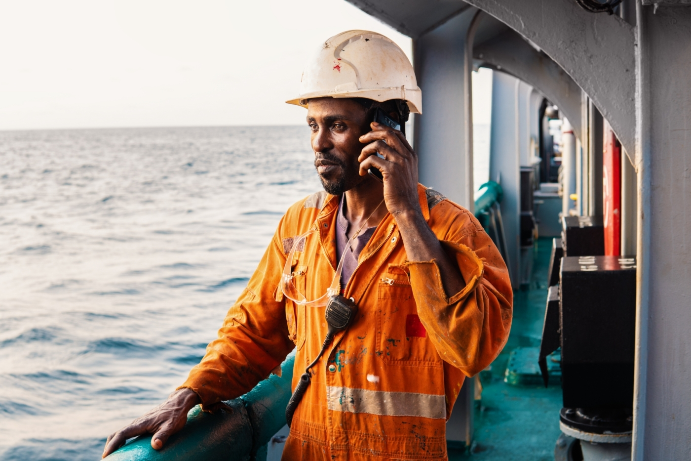A sailor on the deck of a ship, talking on a phone and staring at the horizon.