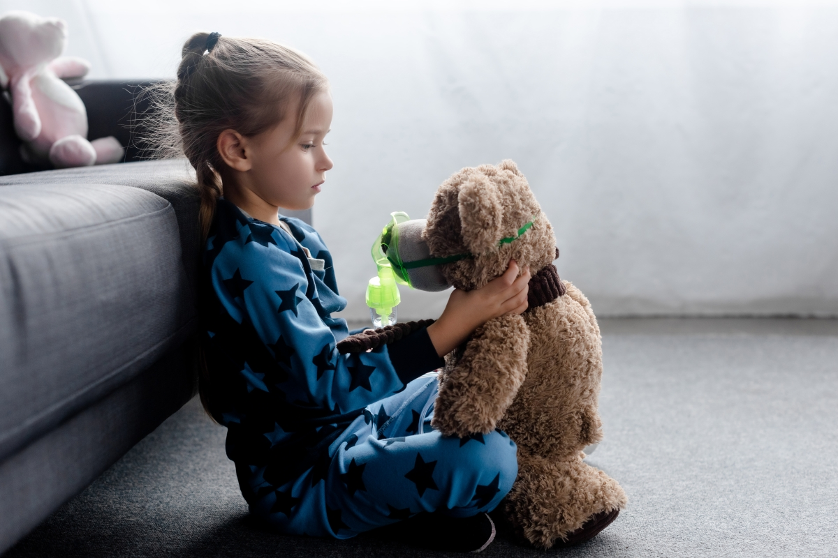 Girl looking at teddy bear wearing oxygen mask